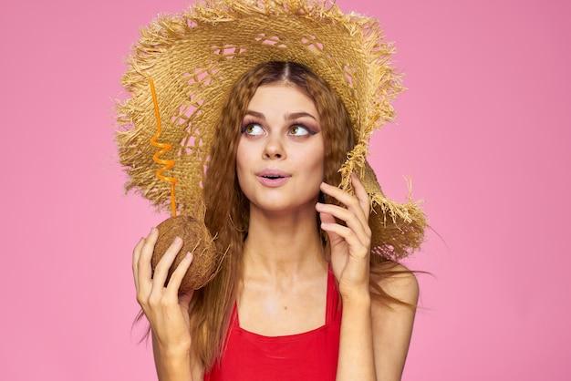 Vrouw met kokosnootcocktail in de zomerroze van de strohoed het exotische vakantie