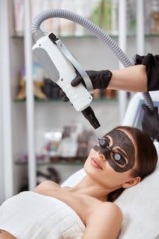 Vrouw met koolstofmasker op gezicht ontvangen laserprocedures in zwarte bril door schoonheidsspecialist in spa salon, verticaal schot og vrouw in spa met gezichtsbehandeling