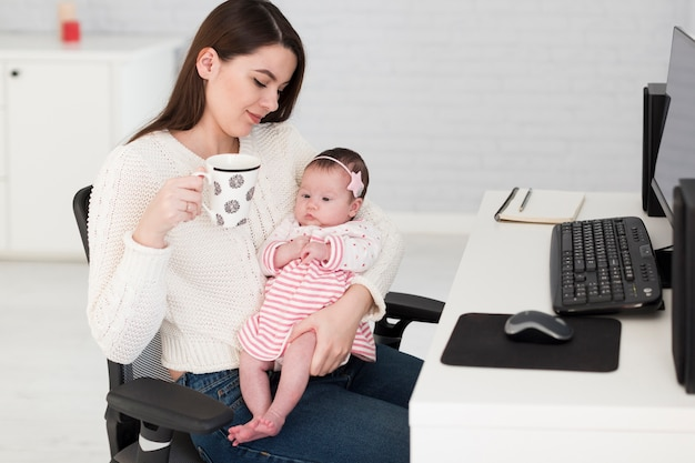 Vrouw met kop en dochter op kantoor