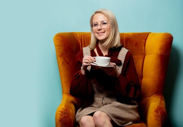 Vrouw met kop van koffiezitting in leunstoel op blauwe backgorund