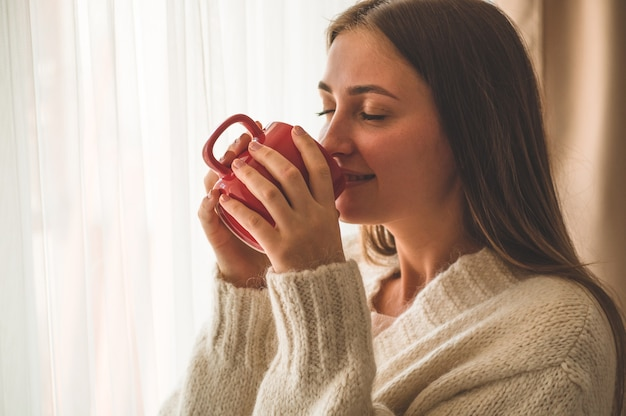 Vrouw met kop warme drank bij het raam. goedemorgen met thee. herfst wintertijd