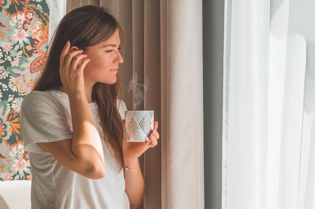 Vrouw met kop warme drank bij het raam. kijkend naar het raam en drink thee. goedemorgen met thee. herfst wintertijd