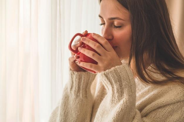 Vrouw met kop warme drank bij het raam