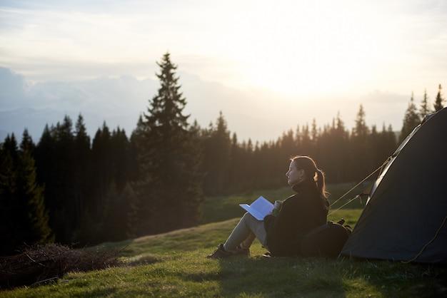 Vrouw met kopje koffie en boek bij de tent