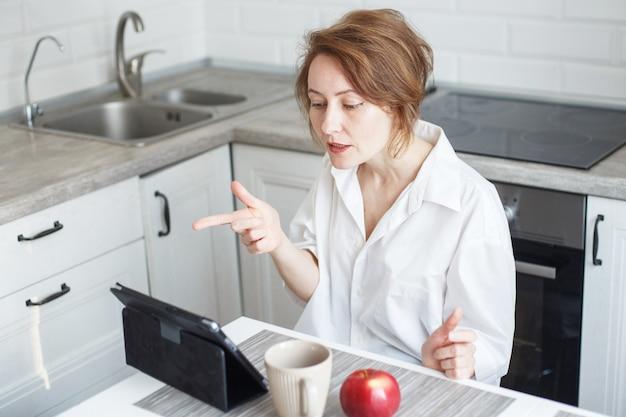 Vrouw met kopje koffie of thee met behulp van laptop in de keuken thuis