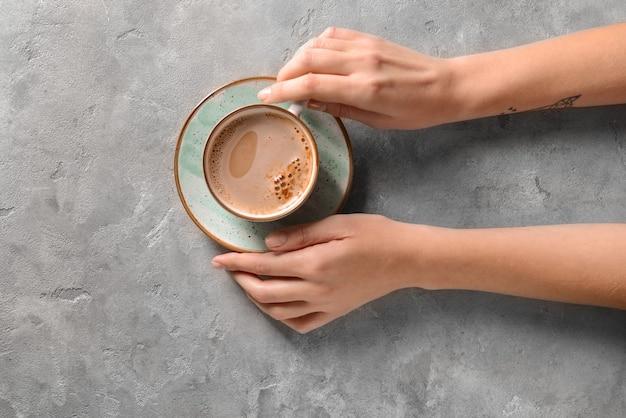 Vrouw met kopje koffie op grijs, bovenaanzicht
