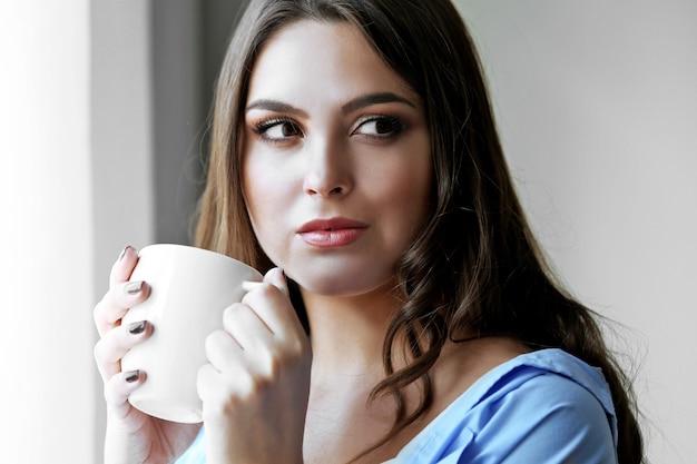 Vrouw met kopje koffie staande in de buurt van raam in de kamer
