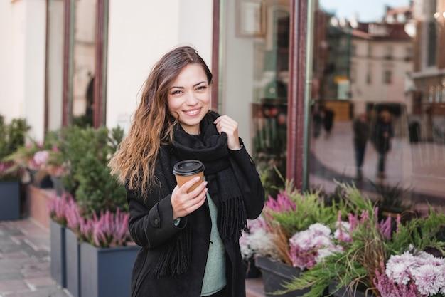 Vrouw met kopje op de stedelijke achtergrond