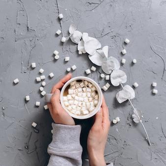 Vrouw met kopje warme koffie op grijs gecementeerde tafel, close-up foto van handen in warme trui met mok, winterochtend concept, bovenaanzicht