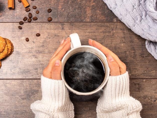Vrouw met kopje warme koffie op rustieke houten tafel, close-up foto van handen