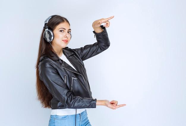 Vrouw met koptelefoon die de grootte van iets laat zien.