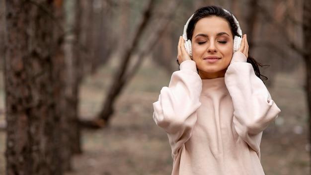 Vrouw met koptelefoon in de natuur