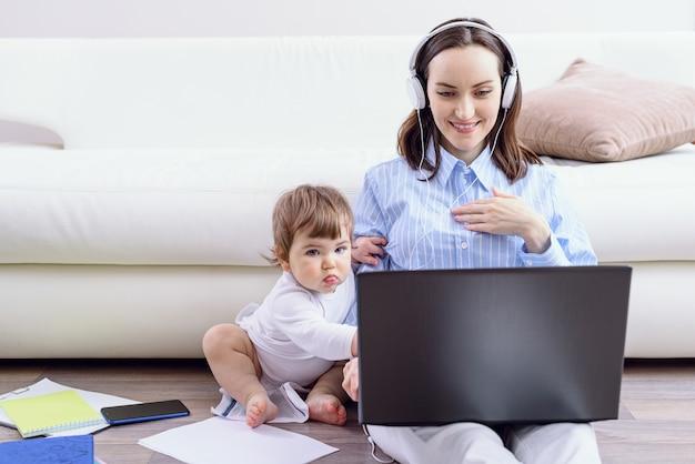 Vrouw met koptelefoon kijkt naar laptopscherm, kind zit naast haar