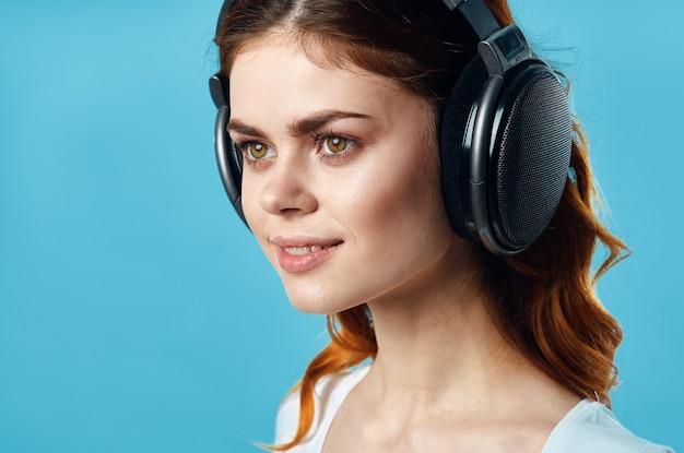 Vrouw met koptelefoon luisteren naar muziek entertainment technologie mode blauwe achtergrond