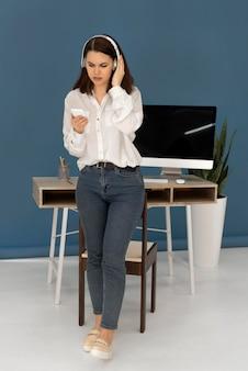 Vrouw met koptelefoon met behulp van mobiel