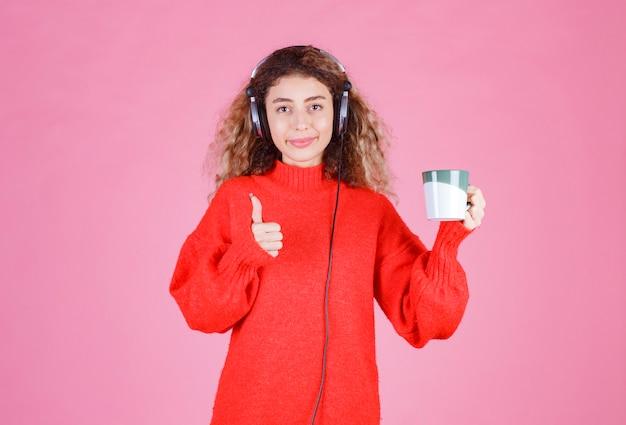 Vrouw met koptelefoon met een koffiekopje.