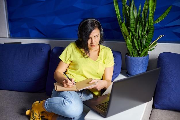 Vrouw met koptelefoon studeren online met behulp van notebook, laptop, het schrijven van notities