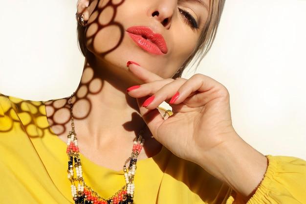 Vrouw met koralen lippen en nagels in een gele jurk op een lichte achtergrond met een schaduwpatroon op haar gezicht.