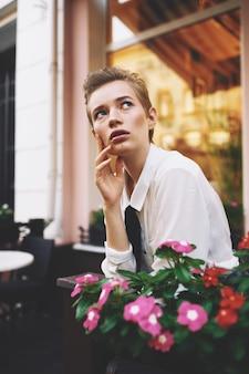 Vrouw met kort haar dichtbij gebouw en ingemaakt bloemenontwerp