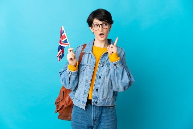 Vrouw met kort haar die een vlag van het verenigd koninkrijk houdt die op blauwe muur wordt geïsoleerd die een idee denkt dat de vinger omhoog richt