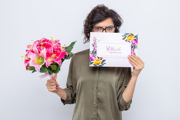Vrouw met kort haar die een wenskaart en een boeket bloemen vasthoudt en er bezorgd uitziet om de internationale vrouwendag 8 maart te vieren
