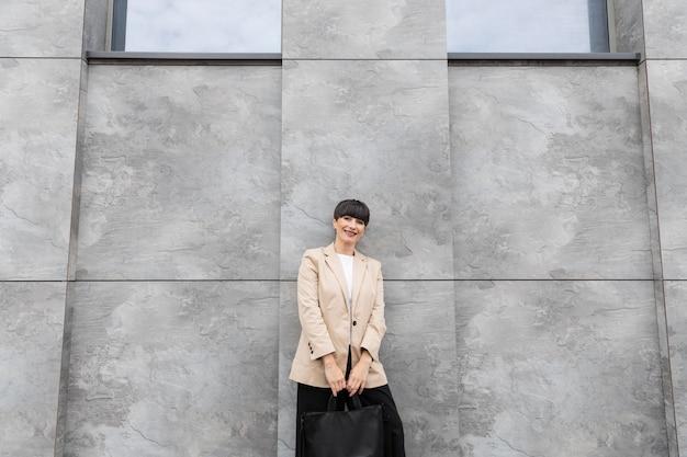 Vrouw met kort haar die haar handtas vasthoudt