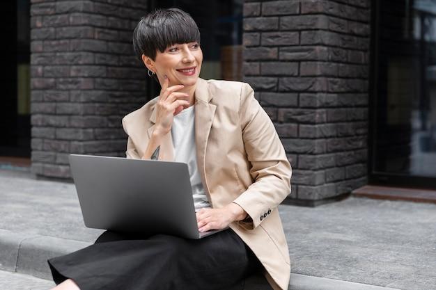 Vrouw met kort haar die haar laptop controleert
