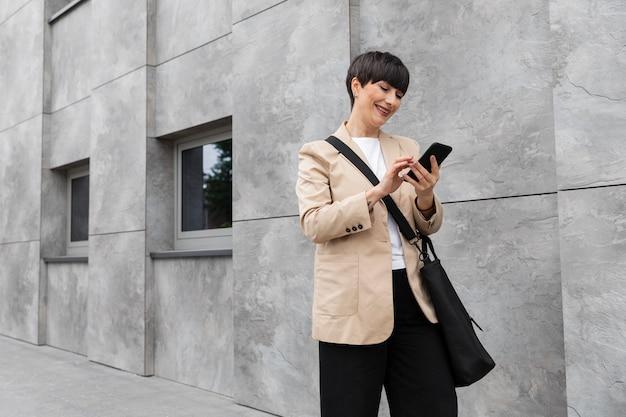 Vrouw met kort haar die haar telefoon buiten controleert