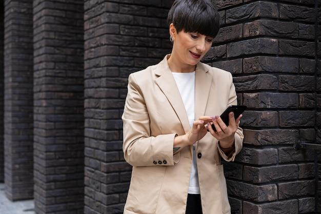 Vrouw met kort haar die haar telefoon vasthoudt