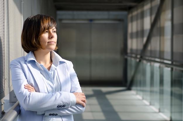 Vrouw met kort haar, gekleed in een wit overhemd dat zich dichtbij de glazen van een viaduct bevindt
