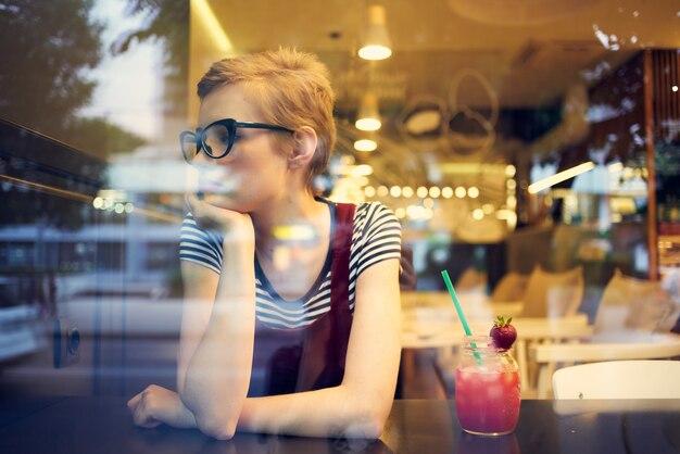 Vrouw met kort haar in een bril zit in een café aan een tafel met een ontspannende cocktail