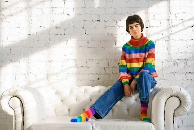 Vrouw met kort haar in een regenboog trui en sokken zit op een witte sofa, het concept van seksuele minderheden