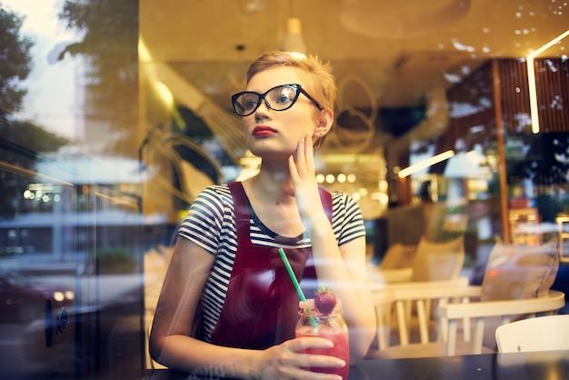 Vrouw met kort haar in een restaurant met cocktailrustdrank