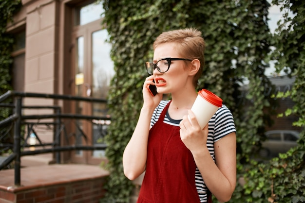 Vrouw met kort haar kopje koffie met een bril praten aan de telefoon