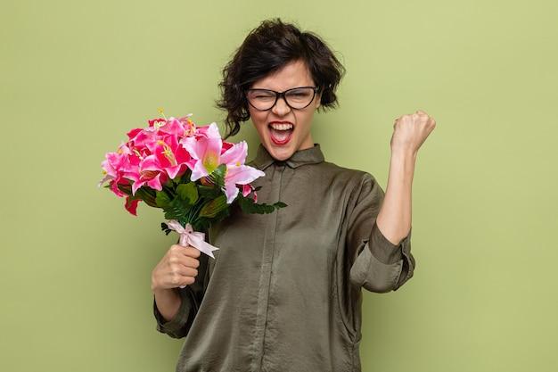 Vrouw met kort haar met boeket bloemen kijkend naar camera blij en opgewonden gebalde vuist vieren internationale vrouwendag 8 maart staande over groene achtergrond