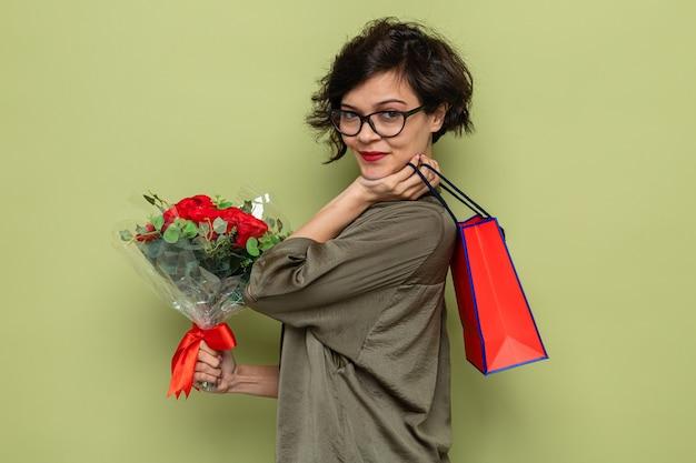 Vrouw met kort haar met een boeket bloemen en een papieren zak met geschenken die er blij en tevreden uitziet