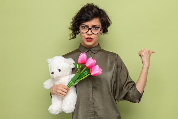 Vrouw met kort haar met een boeket tulpen en teddybeer, kijkend met een serieus gezicht dat met de duim naar achteren wijst