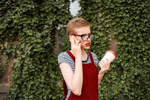 Vrouw met kort haar met een bril op straat praten aan de telefoon kopje koffie