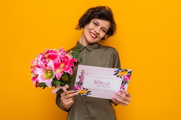 Vrouw met kort haar met een wenskaart en een boeket bloemen die er gelukkig en tevreden uitziet en vrolijk lacht en de internationale vrouwendag 8 maart viert