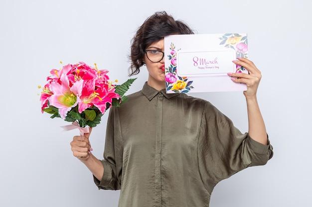 Vrouw met kort haar met een wenskaart en een boeket bloemen die verward kijkt en viert internationale vrouwendag 8 maart