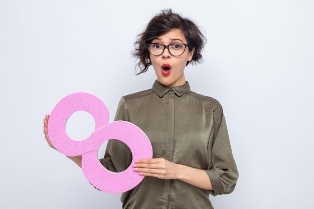 Vrouw met kort haar met nummer acht gemaakt van karton kijkt verrast, internationale vrouwendag, 8 maart