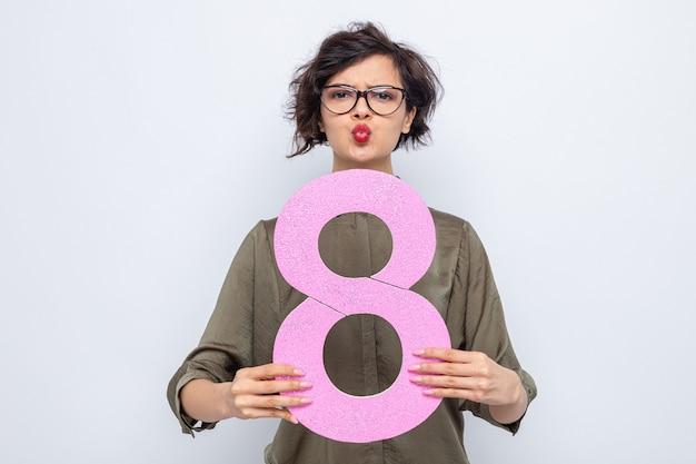 Vrouw met kort haar met nummer acht gemaakt van karton ziet er verward uit en houdt lippen vast alsof ze gaat kussen en viert internationale vrouwendag 8 maart