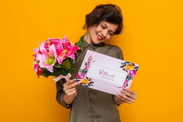 Vrouw met kort haar met wenskaart en boeket bloemen blij en tevreden glimlachend vrolijk internationale vrouwendag 8 maart vieren staande over oranje achtergrond