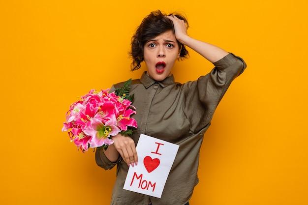 Vrouw met kort haar met wenskaart en boeket bloemen kijkend naar camera verbaasd en verrast vieren internationale vrouwendag 8 maart staande over oranje achtergrond