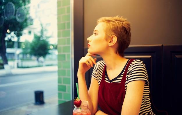 Vrouw met kort haar zit in een café met een cocktail ontspannend genot