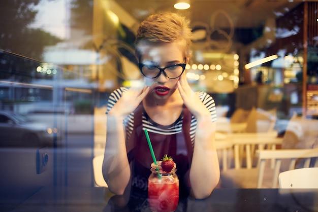 Vrouw met kort haar zittend aan een tafel in een café cocktail drinken eenzaamheid