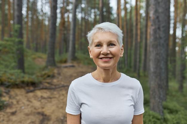 Vrouw met kort kapsel poseren buitenshuis met pijnbomen