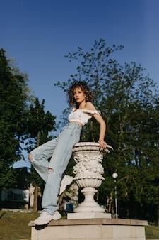 Vrouw met kort krullend haar in spijkerbroek en crop top poseren buiten naast een standbeeld