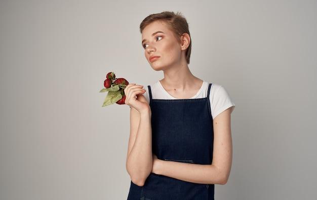 Vrouw met korte kapselbloemen in handen van elegante stijlcosmetica