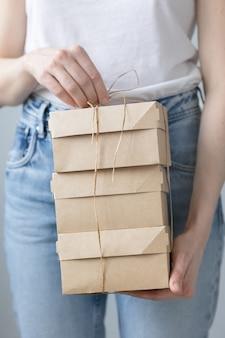 Vrouw met kraft-kartonnen dozen eten of kleding bezorgen moderne manieren om eten te kopen met bezorging